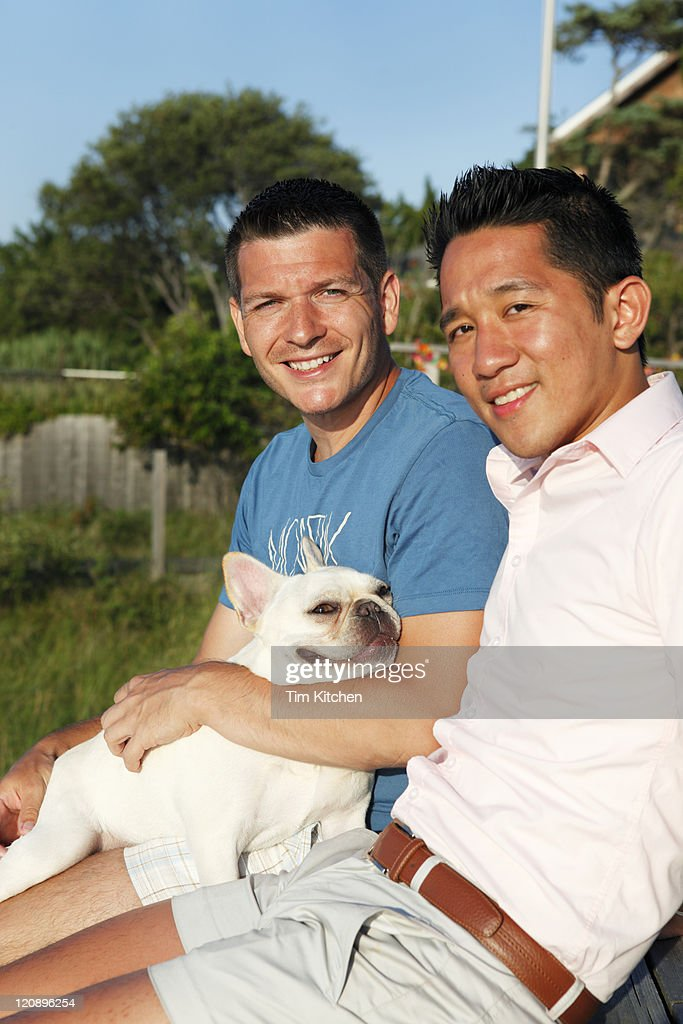Male couple and dog relaxing outdoors in summer : Stock Photo
