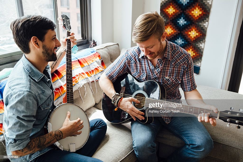 Male couple at home, play guitar and banjo, laughing