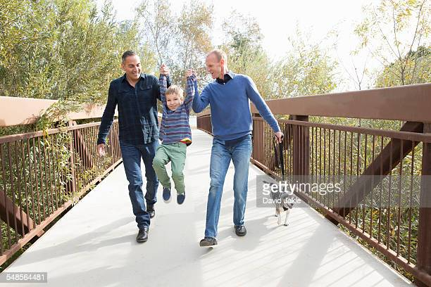 Male couple lifting up son and walking dog in park