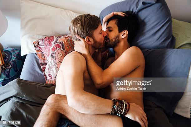 Male couple, partially dressed, lying on bed, kissing