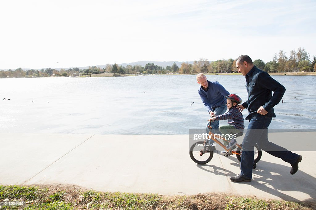 Male couple running next to son on bicycle in park