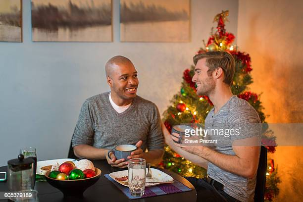 Male couple sitting at table, having breakfast together, Christmas tree in background