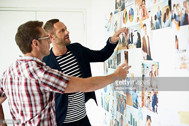 Male coworkers discussing photos