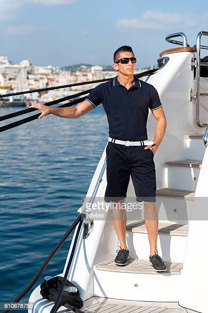 Male crew member standing on yacht