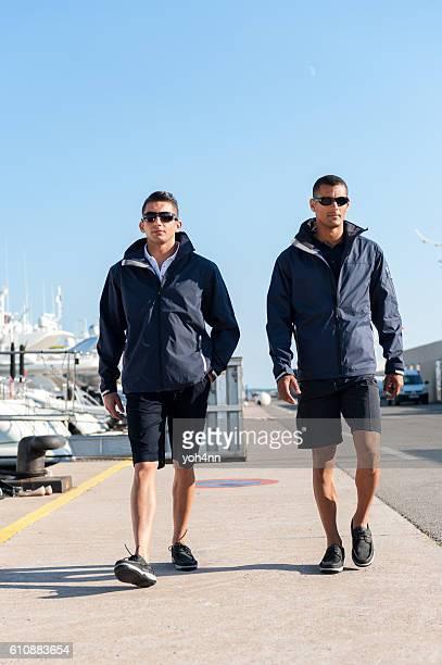 Male crew members walking at harbor