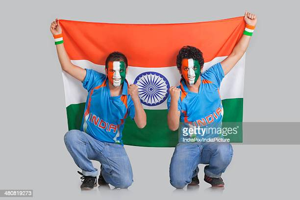 Male cricket fans with face painted in tricolor holding Indian flag over gray background