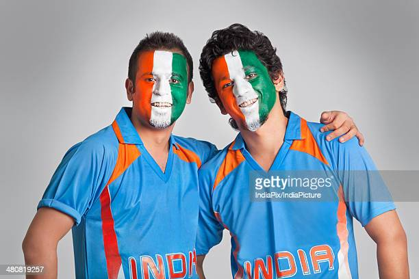 Male cricket fans with face painted in tricolor standing together over gray background