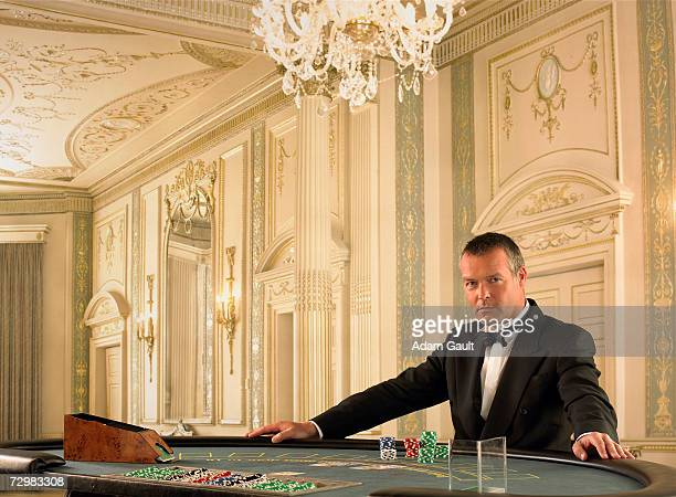 Male croupier at Blackjack table in casino, portrait