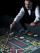 Male croupier at craps table, gathering bets with rake