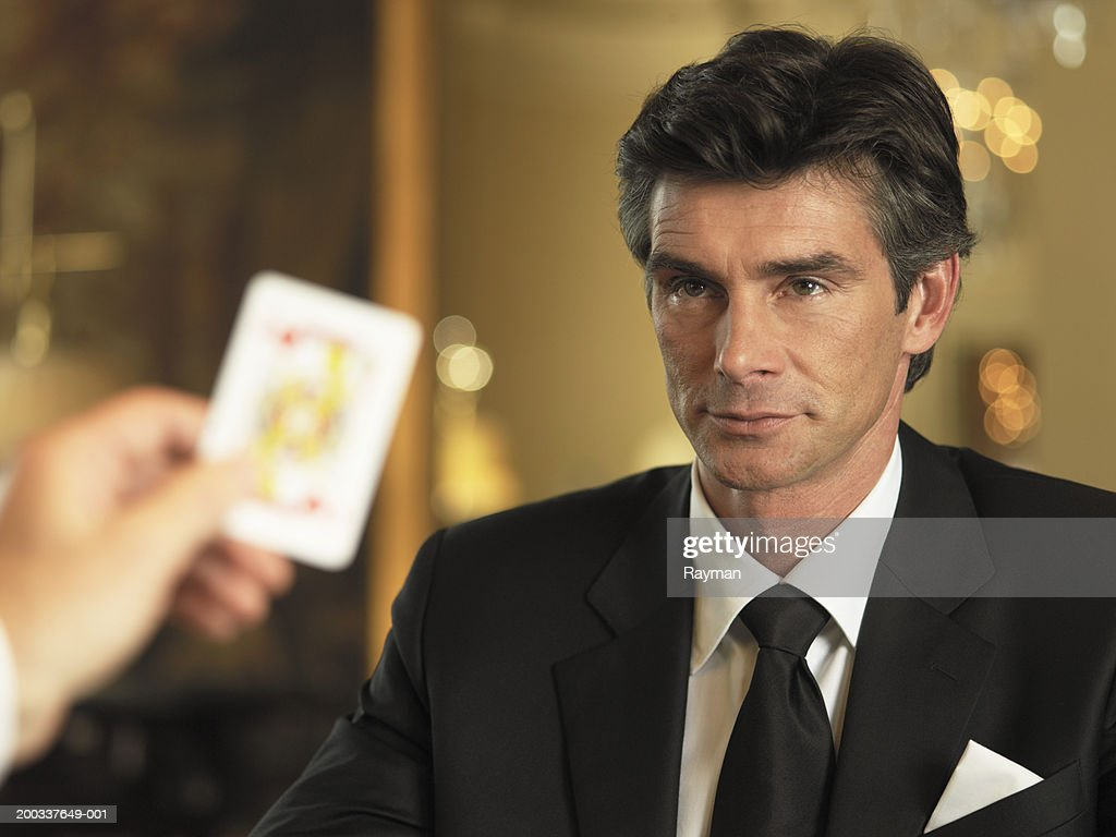 Male croupier dealing card to man in casino