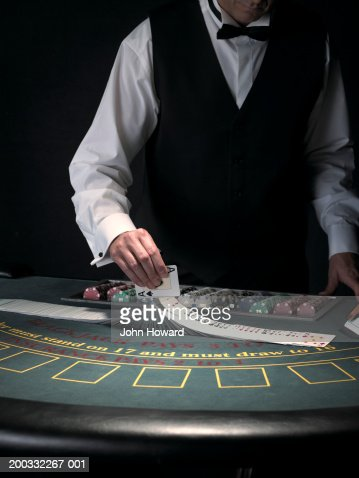 Male croupier extravagantly shuffling cards at Blackjack table