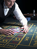Male croupier gathering pile of chips at roulette table