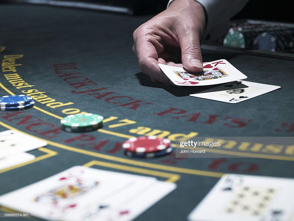 Male croupier holding card at Blackjack table, close-up : Photo
