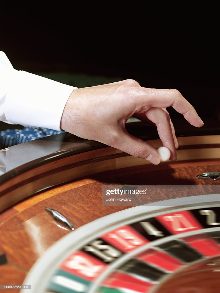Male croupier placing ball on roulette wheel, close-up