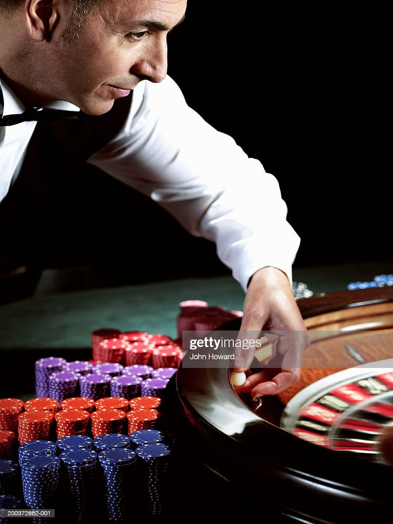 Male croupier placing ball on roulette wheel (blurred motion)