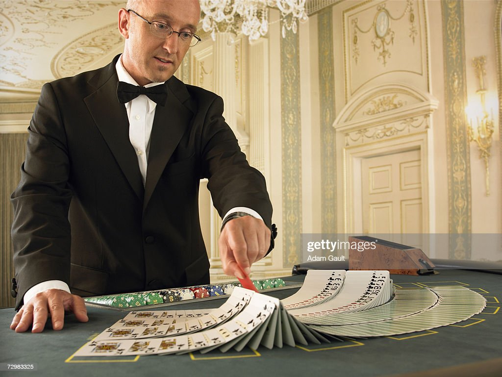 Male croupier preparing cards at Blackjack table in casino