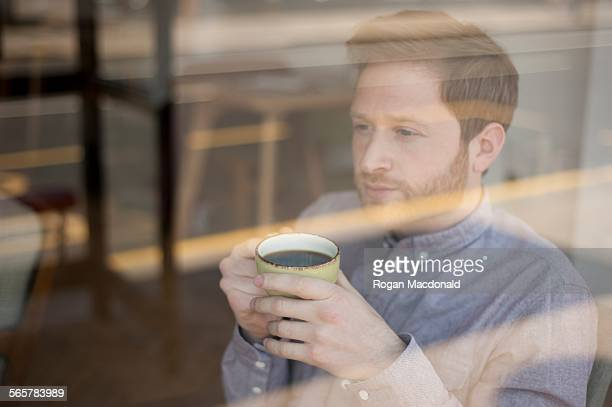 Male customer behind cafe window drinking coffee and gazing