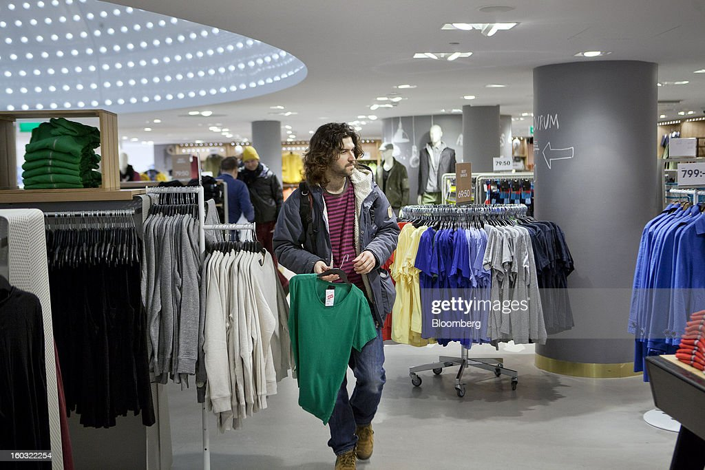 A male customer carries a t-shirt to the sales counter inside a Hennes & Mauritz AB (H&M) store in Stockholm, Sweden, on Tuesday, Jan. 29, 2013. Hennes & Mauritz AB, Europe's second-largest clothing retailer, reported sales growth that beat analysts' estimates for a second consecutive month as the chain offered markdowns in advance of the Christmas holiday. Photographer: Casper Hedberg/Bloomberg via Getty Images