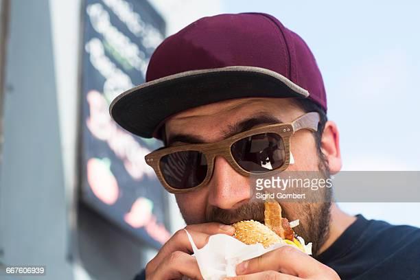 Male customer eating hamburger from fast food van