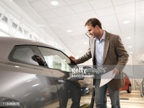 Male customer holding paper, looking at car with hand touching car in car dealership : Stock Photo