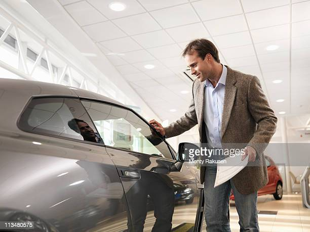 Male customer holding paper, looking at car with hand touching car in car dealership