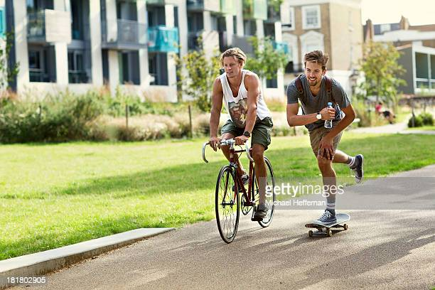 male cyclist and skateboarder in park