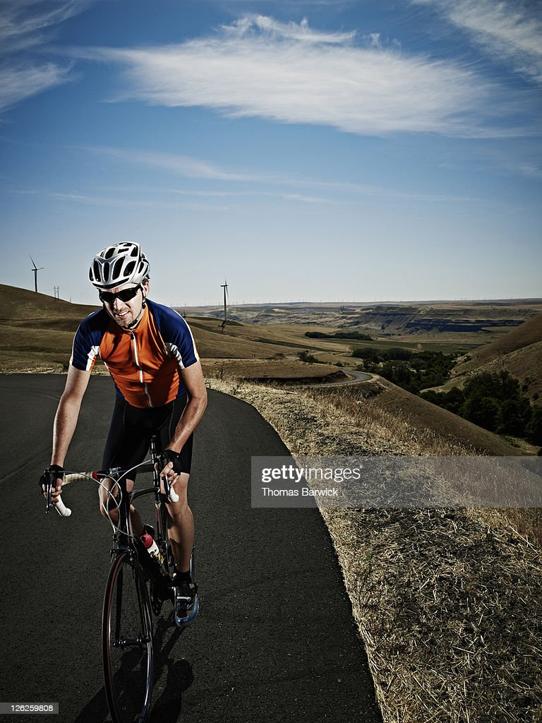 Male cyclist climbing hill on empty road : Stock Photo