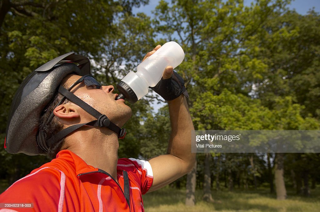 Male cyclist drinking from water bottle outdoors, close-up : Stock Photo