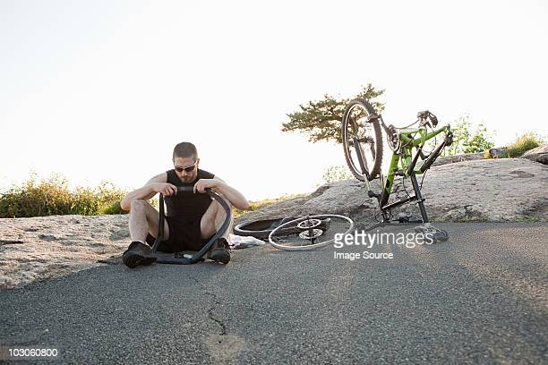 Male cyclist fixing punctured tyre