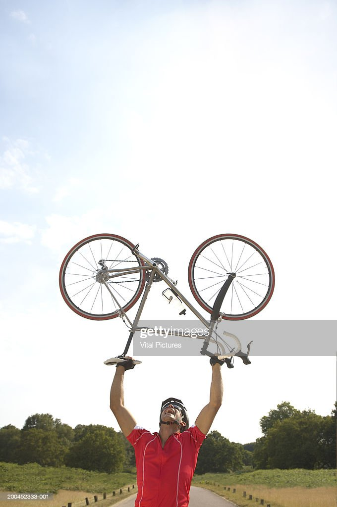Male cyclist lifting bicycle above head outdoors : Stock Photo