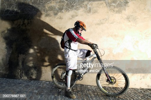 Male cyclist on bike in cobbled street, side view : Stock Photo