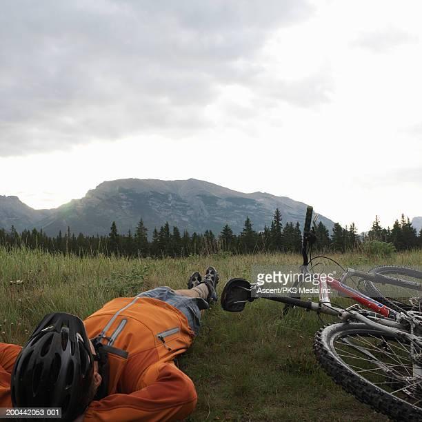 Male cyclist relaxing in mountain meadow, rear view, sunrise