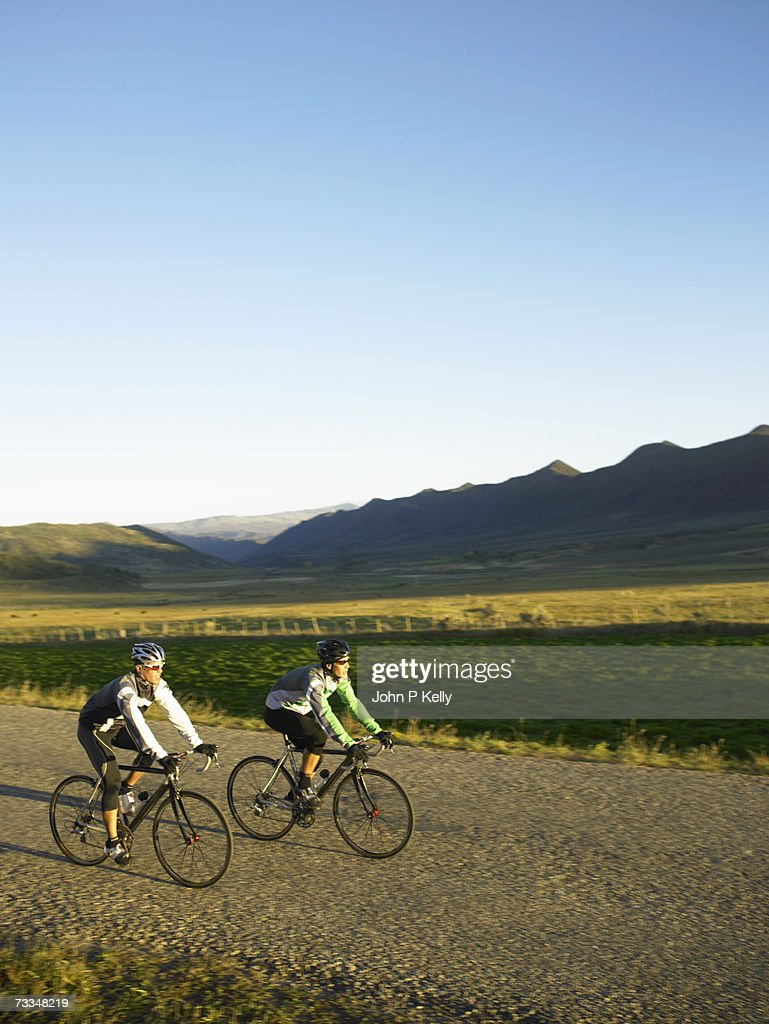 Male cyclist riding bicycle on country road, side view : Stock Photo