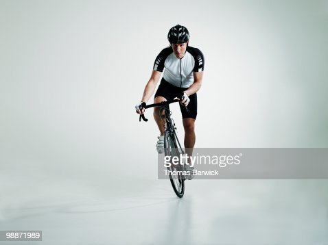 Male cyclist standing in pedals riding bike : Stock Photo