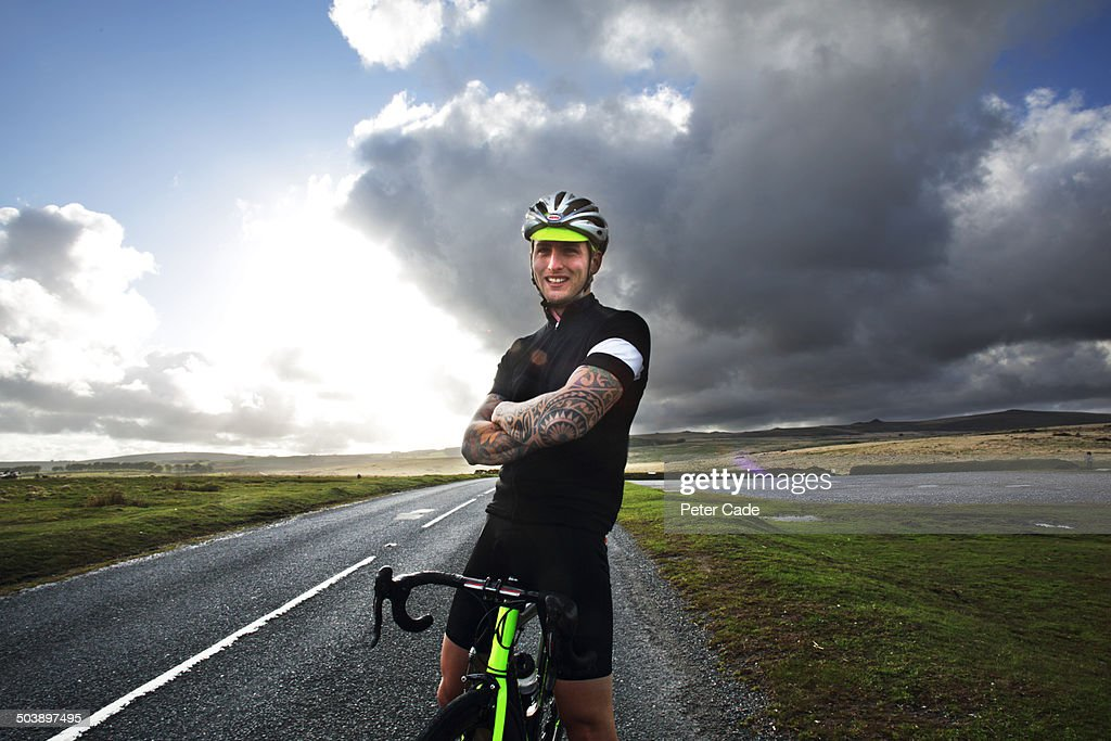 Male cyclist stood on bike smiling at camera