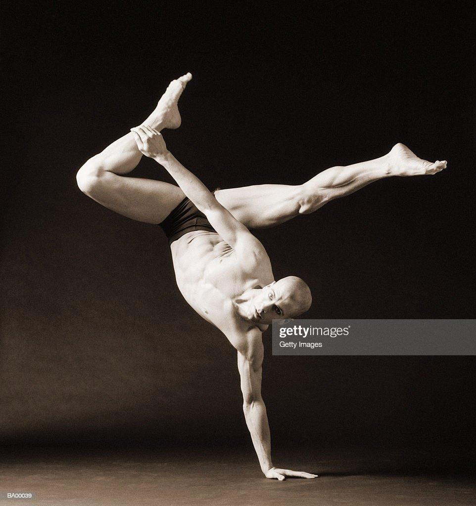 Male dancer balancing on one hand, (B&W) : Stock Photo