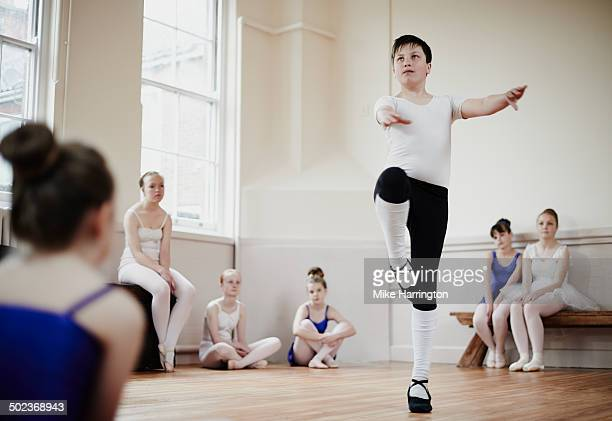 Male dancer performing pirouette in front of class