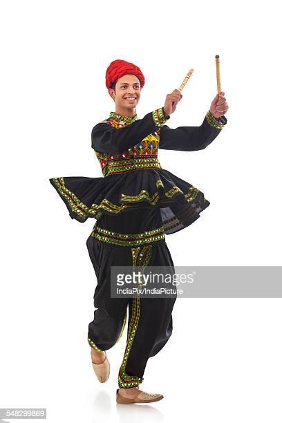 Male dandiya dancer dancing with sticks