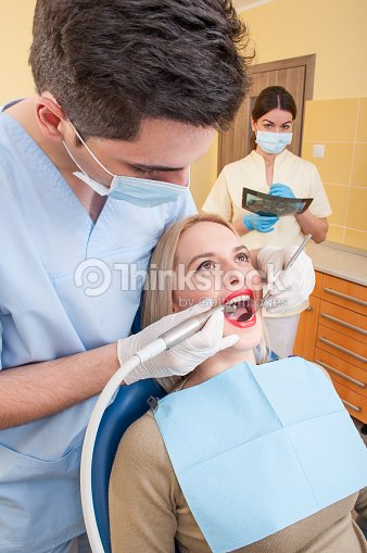 Male Dentist And Female Assistant Working Stock Photo