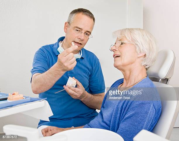 Male dentist talking with female patient