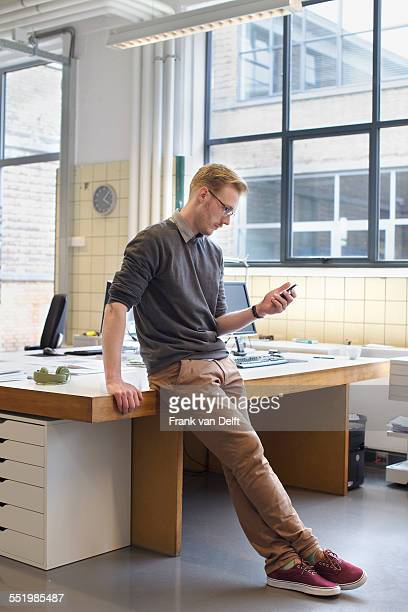 Male designers looking smartphone in creative office