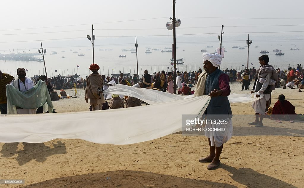 Male devotees hold long stripes of clothing used to wrap themselves while bathing called Dhothis after they took a dip at the Sangham or confluence of the Yamuna and Ganges river at the Kumbh Mela celebration in Allahabad on January 13, 2013. Worshippers believe a dip in the holy waters cleanses them of their sins. The Kumbh Mela in northern India, starting January 13 and stretching over 55 days, attracts ash-covered holy men who run into the frigid waters, a smattering of international celebrities, as well as millions upon millions of ordinary Indians to Allahabad, at the confluence of the rivers Yamuna and Ganges.