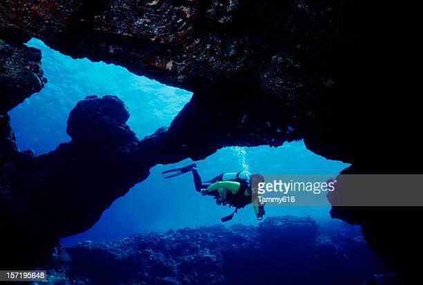 Homme plongeur dans une grotte sous-marine