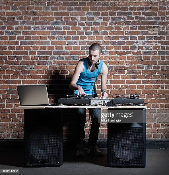 Male DJ Mixing with Decks and Laptop