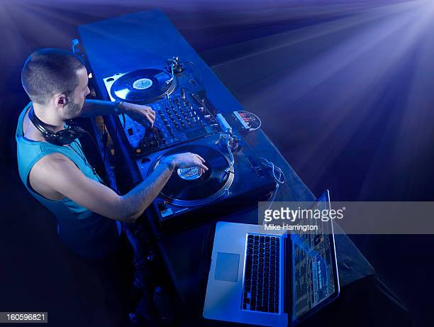 Male DJ Using Decks and Laptop