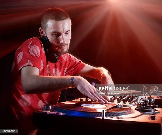 Male DJ Using Decks in Nightclub