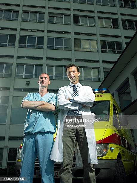 Male doctor and nurse standing by ambulance outside hospital, portrait