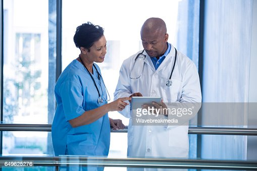Male doctor and nurse using digital tablet in corridor : Stock Photo