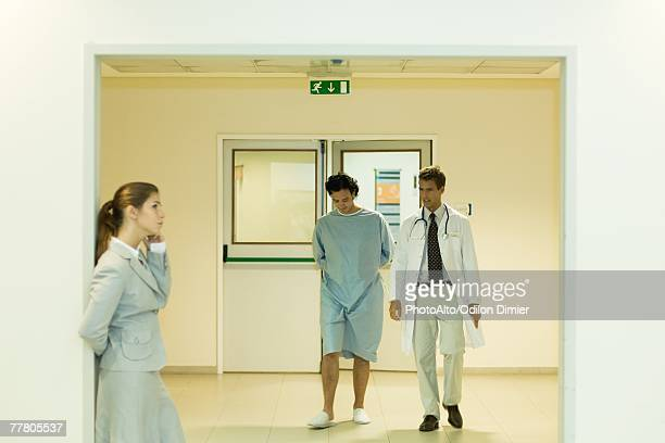 Male doctor and patient walking together in hospital corridor, woman using cell phone in foreground