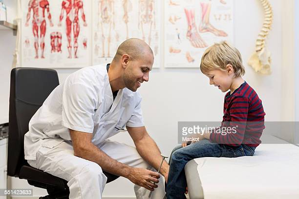 Male doctor checking knee reflexes of boy at orthopedic clinic